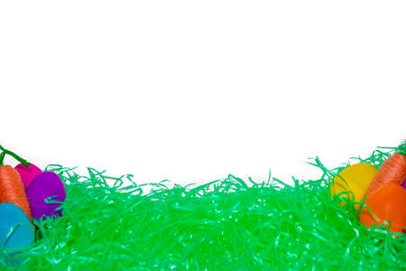 Green Easter Grass, Colorful Eggs, and Carrots With a Pure White Background Behind It
