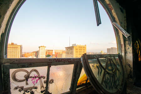 Looking Out a Large and Broken Arched Window at a City Skyline and Clear Sky in an Abandoned Building