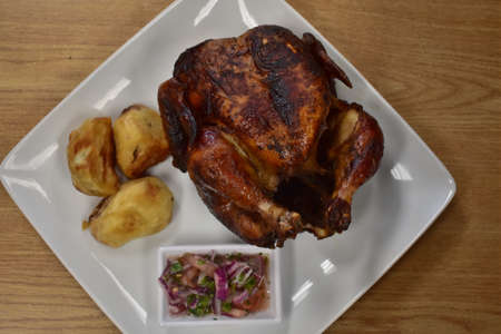 Rotisserie Chicken on a White Plate on a Wooden Table With Potatoes and a Small Salad Next to It