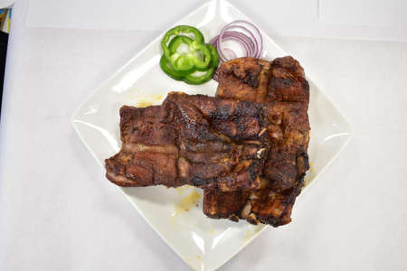 A Well-Done Rack of Ribs Plated on a White Background Archivio Fotografico