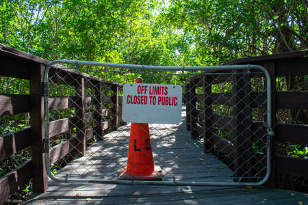 A Boardwalk With a Fenced Off Section With a Traffic Cone Behind It Stating That It's Off Limits to the Public