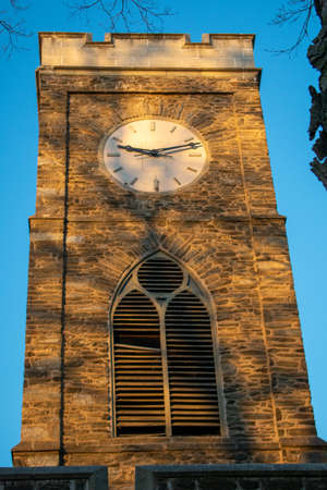 A Clocktower bathed in glowing orange sunlight with shadows from a tree Stok Fotoğraf