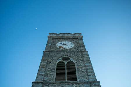A Church's Cobblestone Clock Tower on a Clear Blue Sky Stok Fotoğraf