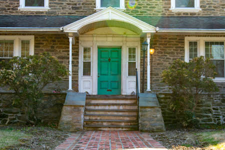 A Teal Front Door on a Suburban Home With a Brick Path Leading Up to It