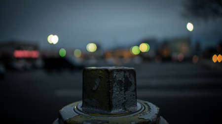 The Top of a Silver Fire Hydrant With a Blurred Shopping Center Behind It