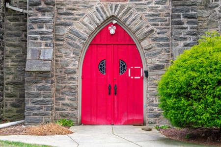 A Bright Red Door in a Cobblestone Church Wall With a Bush on the Side