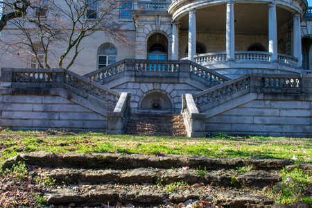 A Courtyard With Steps and a Large Balcony With Pillars Above at Elkins estate