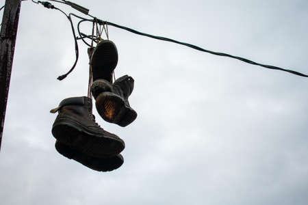 Boots Hanging From a Thin Wire on an Overcast Sky