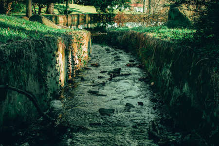 A Man Made Stream With Cobblestone Walls Flowing Into a Lake at Elkins Estate