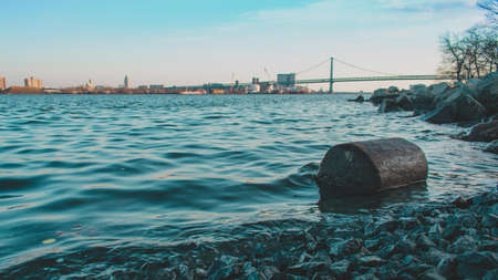 A Log on the Shore of the Deleware River at Penn Treaty Park With the Ben Franklin Bridge Behind It