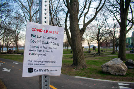 PHILADELPHIA, PENNSYLVANIA - MARCH 26, 2020: A Sign from Philadelphia Parks and Recreation at the Penn Treaty Park States a COVID-19 Alert and Asks Park-Goers to Practice Social Distancing