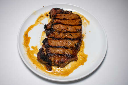 A Perfectly Cooked Steak With Grill Lines Plated on a Pure White Background 版權商用圖片