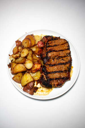 A Perfectly Grilled Steak With Black Grill Lines and Potatoes Plated on a Pure White Background