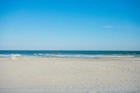 A Large Empty Beach and Ocean With a Lifeguard Chair on a Clear Blue sky in Wildwood New Jersey