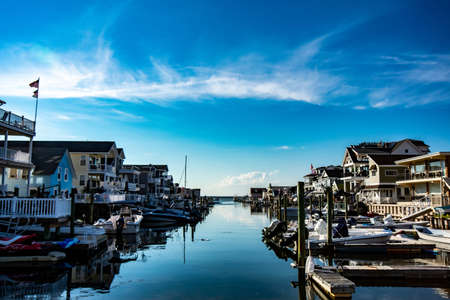 A View of a Canal With Boats and Homes on Each Side on a Clear Blue Sky With Gorgeous Clouds in Wildwood New Jersey