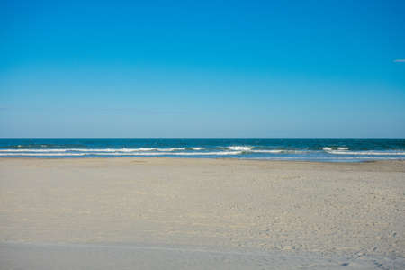 An Empty Beach and Ocean With a Clear Blue Sky Behind at Wildwood New Jersey