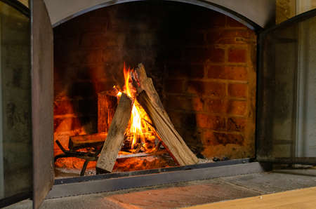 A Bright Orange Fire Burning in an Old Brick Fireplace
