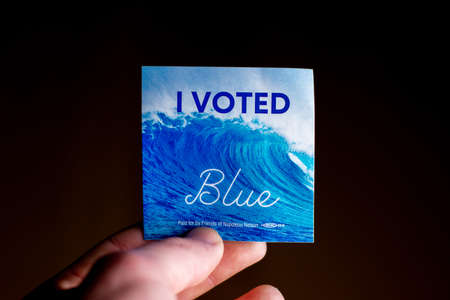 November 3, 2020 - Elkins Park, Pennsylvania: An Election Day Sticker Held by a Hand That Says I Voted Blue With a Wave in the Background on Black