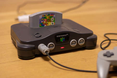 A Nintendo 64 Console With the Power Indicator Light On and Super Mario 64 in the Cartridge Slot and a Controller Plugged Into It 新聞圖片