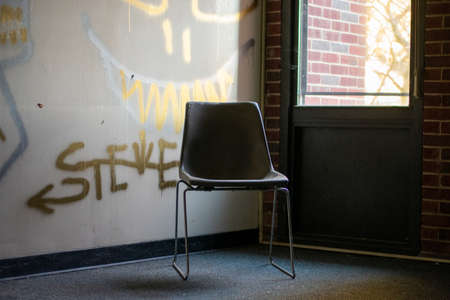 An Empty Chair Next to a Window in a Corner in an Abandoned Building