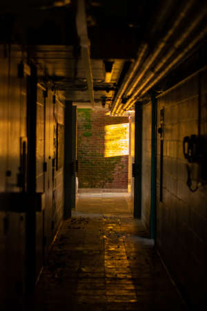 A Dark Hallway Inside an Abandoned Dormatory With Orange Light at the End of It 版權商用圖片