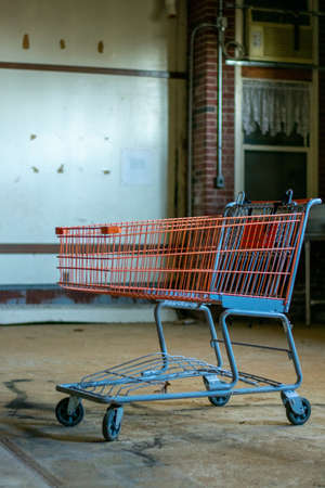 A Red Shopping Cart In a Large Empty Room in a destroyed Abandoned Building