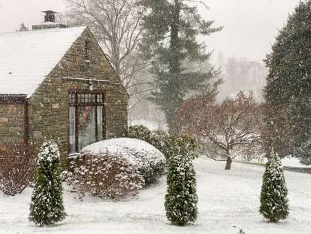 A Cobblestone Home With a Wreath in a Window next to a Suburban Street During a Snowstorm