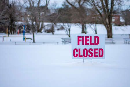 A White Sign With Red Text That says field Closed in a Snow Covered Soccor Field