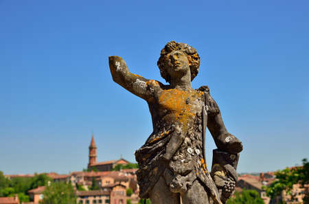 Ancient moss-covered statue in the gardens of the Berbie palace in Albi, France
