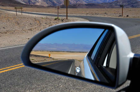Desert road in Death Valley National Park as reflected by a rear-view mirror photo