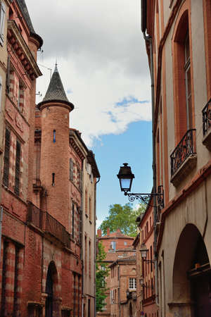 edifice: Narrow historic street with old buildings in Toulouse, France