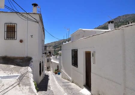Narrow street in the Alpujarras with typical white houses , Andalusia, Spain photo
