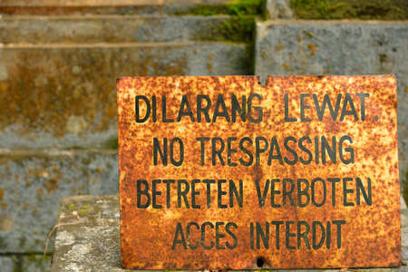 multilingual: Old and rusty multilingual no treppasing sign  english, french, german, indonesian