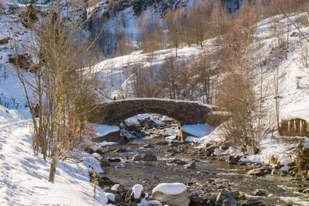 Old bridge on a small river and snowy mountains in the Pyrenees in winter, France photo