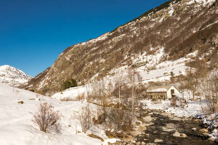 Small river and snowy mountain in the Pyrenees in winter, France photo