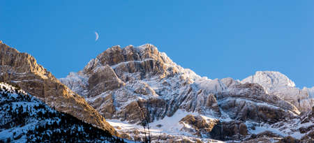 Snowy mountains and the moon at Gavarnie in the Pyrenees, France photo