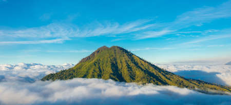 Mountain above the clouds from the rim of the Kawah Ijen volcano, Java, Indonesia Stock Photo