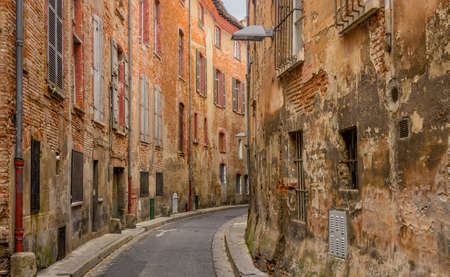 redbrick: Narrow decrepit red brick street in Toulouse, France