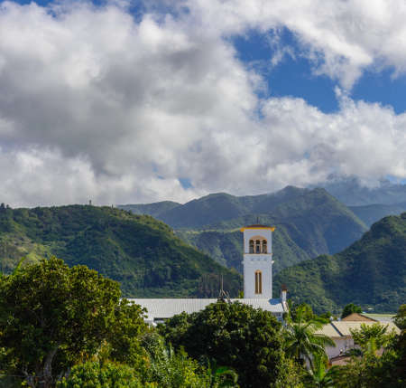 creole: Church with bell tower in lEntre-Deux with mountains in background, la Reunion island Stock Photo