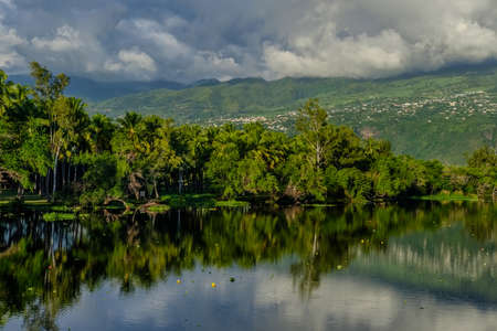 Saint Paul lake, palm trees and clouds in la Reunion island, a french overseas department in the Indian Ocean Imagens