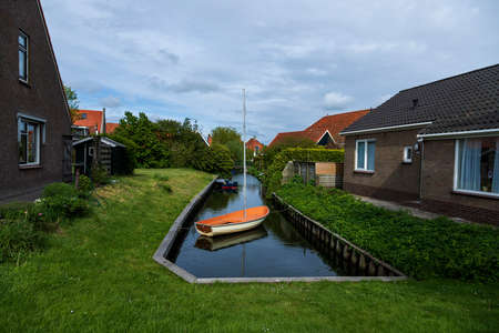 Water canal between houses in Hindeloopen in Holland. There's a boat on the water.