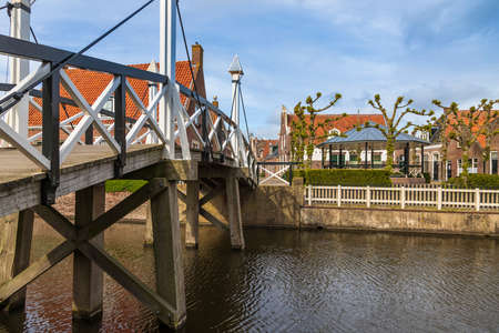 Old wooden bridge over canal in Hindeloopen in the Netherlands. Background is blue sky.