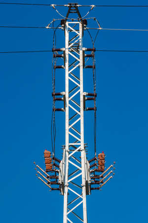 High voltage pole for electricity distribution. Background is blue sky.