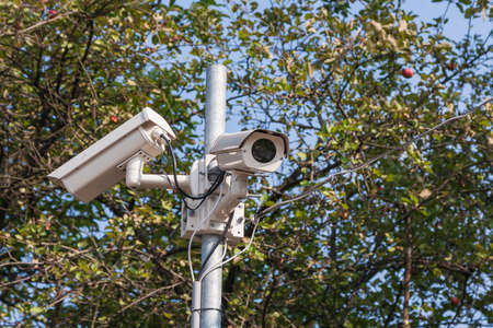 Security cameras to capture the surrounding area. Background are green trees and blue sky. Imagens