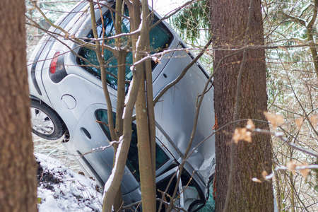 A car that crashed on a snowy road and crashed into a tree. Stok Fotoğraf