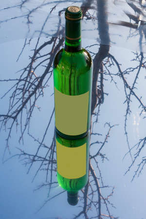 A bottle of white wine stands on a mirror mat. The label is empty