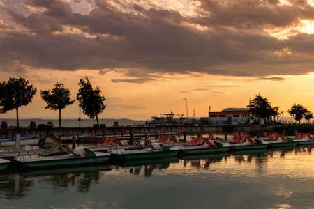Wooden pier with a boat in the town of Podersdorf on Lake Neusiedl in Austria. In the background is a dramatic sunset sky. 免版税图像 - 150364058