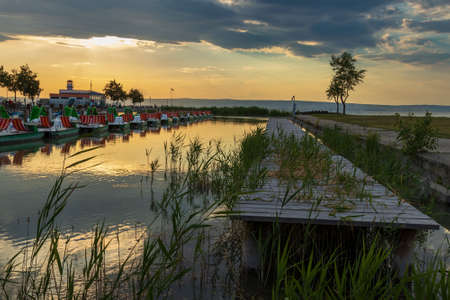 Wooden pier with a boat in the town of Podersdorf on Lake Neusiedl in Austria. In the background is a dramatic sunset sky.