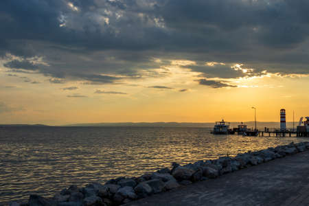Road leading to the lighthouse in the town of Podersdorf on Lake Neusiedl in Austria. In the background is a dramatic sunset sky