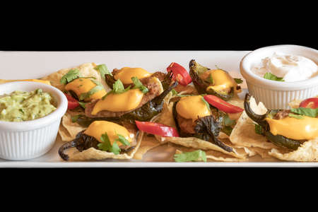 Roasted meat on chips decorated with peppers and cheese. The meat has avocado and garlic dip. The food is on a white plate isolated on a black background.